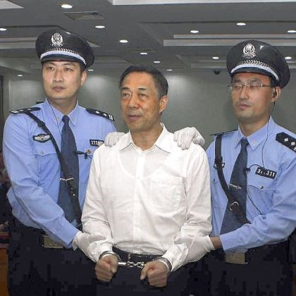 Bo Xilai Politician Bo Xilai, is handcuffed Sunday and held by police officers as he stands at the court in eastern China's Shandong province.
