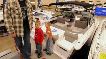 Boat admirer Chris Kirich of Nottingham, Washington County, admires a Four Winds SL222 Deck Boat with sons Kobie, 5, and Austin, 3, at the Miller's Marine display at the Pittsburgh Boat Show on Sunday.