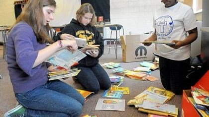 Book drive From left, eighth-grader Molly Wicker, 14, seventh-grader Aubrie Tarris, 12, and sixth-grader Ashley Bridges, 12, sort children's books Tuesday at Quaker Valley Middle School. Molly is leading a collection effort for the African Library project.