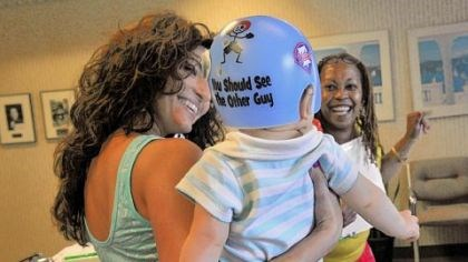 Braylon Jocelyn Corcoran (left) and April Blue, who works at Union Orthotics & Prosthetics, play with Jocelyn's son, Braylon, who wears a helmet to help correct a flat spot on his head.