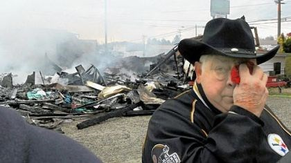 Burley Hartin Valley Billiards owner Burley Hartin dabs his eyes while his business near New Alexandria smolders in the background on Friday.