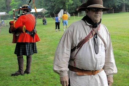 Bushy Run 4 Ed Dammer, right, of South Williamsport, portraying a Ranger, walks past Sam Roha of Delmont, who portrays a bagpiper from the 42nd Royal Highland Regiment (the Black Watch).