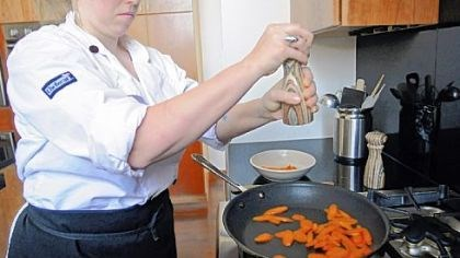 Chef Rachel Lori Chef Rachel Lori seasons fresh sliced carrots with salt and pepper as she sautes them in oil.