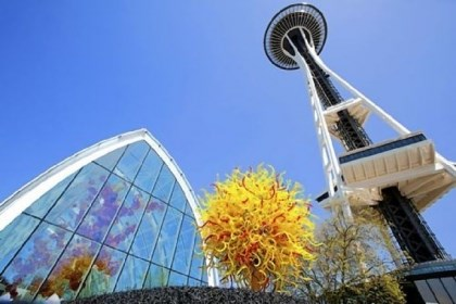 "Chihuly exhibit Chihuly Garden and Glass opened under the Space Needle. The work ""Pacific Sun"" sits in front of The Glasshouse (at left)."