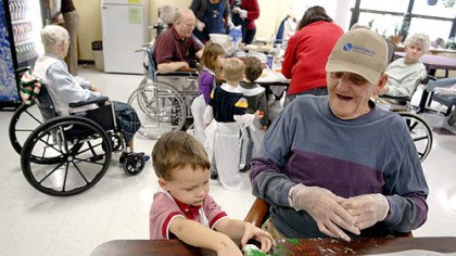 Christmas cookies Bob Fulton, 84, gets help from Tristian Cribbs, 4, while making Christmas cookies at Beacon Ridge, a nursing home in Indiana, Pa.