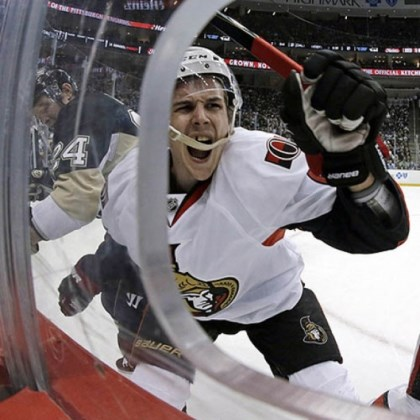 cooke and karlsson Ottawa Senators defenseman Erik Karlsson, center, grimaces as he hits the boards after colliding with Penguins left wing Matt Cooke Thursday night.