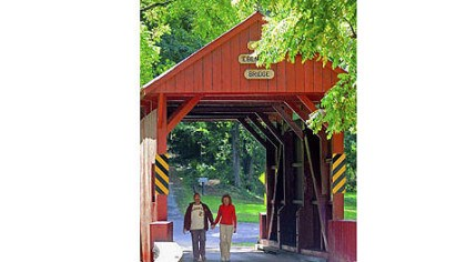 Covered bridge The Rev. Mark Swoger, pastor of Holy Trinity Polish National Catholic Church in Washington, walks hand-in-hand with his wife, Miriam, through the Ebenezer covered bridge in Mingo Creek Park in Nottingham on Wednesday afternoon.