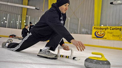 "Delivers the stone Jerrett Covington, 30, of Moon, delivers the stone during a ""learn to curl"" class at the Robert Morris University Island Sports Center on Neville Island."