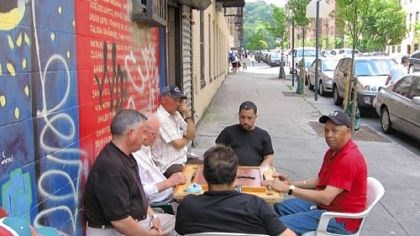 Dominoes on Ellwood Street A group of men play dominoes on Ellwood Street in Washington Heights, New York City, a half block from Pedro Alvarez's apartment building.