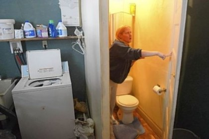 Donna Goldinger points out some of the problems Donna Goldinger points out some of the problems in her Carrick house. She has reported some of them to the Health Department, which found raw sewage flowing into a crawl space, a lack of smoke detectors and other violations. Here, Ms. Goldinger stands near the basement toilet, where the floor, now covered by a board, has collapsed.