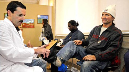 "Dr. Stephen Conti fits Richard Killian Dr. Stephen Conti fits Richard Killian with a new pair of shoes at his ""Our Hearts to Your Soles"" event. Red Wing Shoes at Catholic Charities in Downtown Pittsburgh donated new shoes. Started as a Pittsburgh-oriented effort five years ago, the charity has expanded to 40 sites nationwide with an estimated 400 volunteers. People receive a foot health screening, socks and a pair of shoes."