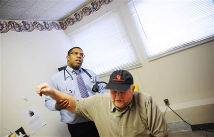 Dr. Zane Gates Dr. Zane Gates examines the shoulder of Vernon Smith of Duncansville at a free clinic for the working poor, Partnering for Health, in Altoona earlier this month.
