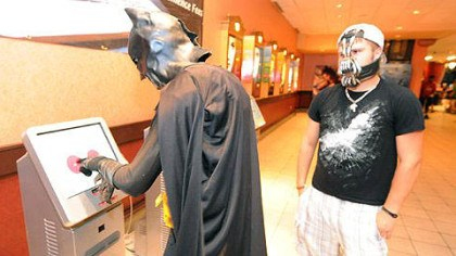 "Dustin Briggs Dustin Briggs, dressed as Batman, buys a ticket to the midnight showing of ""The Dark Knight Rises"" at AMC Loews Waterfront, while Tanner Kefover, dressed as Bane, looks on."