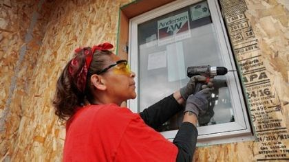 Eco-Village, a Habitat for Humanity project Nakeia Dismond, an Eco-Village home owner, helps install the first window in her River Falls, Wis., home.The energy-saving window is one of many energy-efficient features used in Eco-Village, a Habitat for Humanity project.
