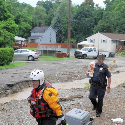 Emergency crews Emergency crews drag a sled containing a beagle named Snuffy after heavy rain flooded and destroyed portions of Irwin Street and Cemetery Street in Elizabeth Borough on July 10.