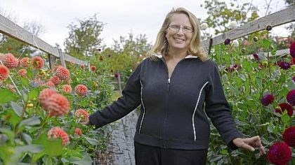 Evy Rogers Alpha Dahlias owner Evy Rogers stands with 'Rose Toscano,' left, and 'Ivanetti' dahlias, right.