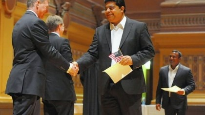 Farukh Naqvi Farukh Naqvi, originally of India, receives a certificate and flag during the naturalization ceremony.