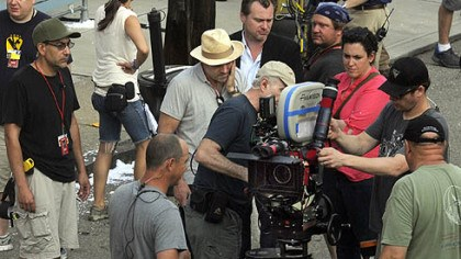Film's leaders A camera near director Christopher Nolan, center in suit coat, and prdoucer Emma Thomas (in pink) is prepped for a scene.