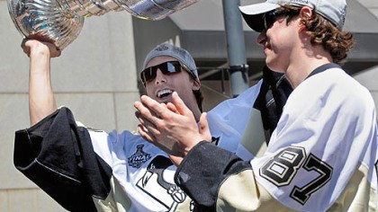 Fleury and Crosby Penguins goalie Marc-Andry Fleury holds up the Stanley Cup as he rides with captain Sidney Crosby along Grant Street.