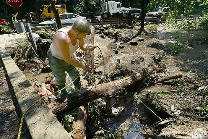 flood1 George Slagle ties a rope to a log Thursday to remove it from a stream near Route 48 in Elizabeth Township following Wednesday's flash flooding.