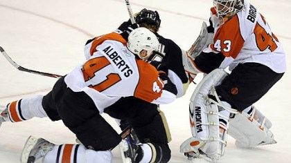 Flyers to the left and right Jordan Staal is sandwiched between Flyers Andrew Alberts and goaltender Martin Biron in overtime.
