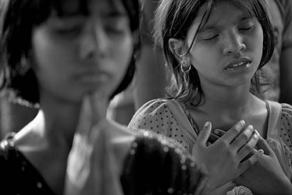 Girls in church service Christian girls pray during a service in Koraput, India. Members of the Hindu majority forced Christians to leave their homes and settle here. The photography show is at 707 Penn Gallery.