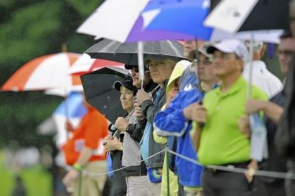 Golf 2 Fans watch through a passing shower as players putt on the first hole.