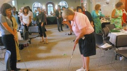 Golf tip Sandy Thomas demonstrates a trick about putting stance for a women's entrepreneurship luncheon Tuesday at Chatham University: Hold a ball to your eye, let it drop, and if you are in the correct stance over the ball, the falling ball will hit the one on the ground.