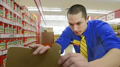 Good Cents Manager Josh Leroux puts pricing stickers on products Thursday at the new Good Cents grocery store on McKnight Road. The store opens Sunday.