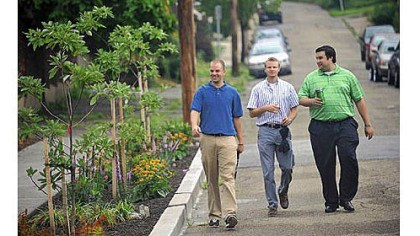 Greenfield From left, The Penn State Center interns Derek Thomas, Preston Linck and Justin Polosky walk past the newly created Four Mile Run bioswale, a stormwater mitigation project that they helped create, before a ribbon cutting Friday on Saline Street in Greenfield.