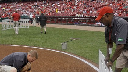 Grounds crew Members of the Reds' grounds crew paint a sign in the dirt behind home plate directing fans to an Internet site where they can vote for Reds players to the National League All-Star team.