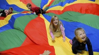 Gym dandies Students Milana Starostina, right, and Isabella Cuomo, second from right, play on a parachute during gym class Thursday with their preschool
