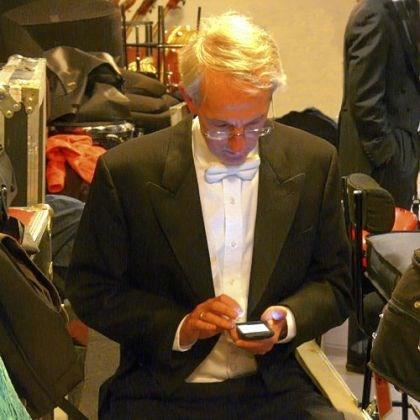 Hampton Mallory PSO cellist Hampton Mallory checks his email amid backstage chaos in Paris.
