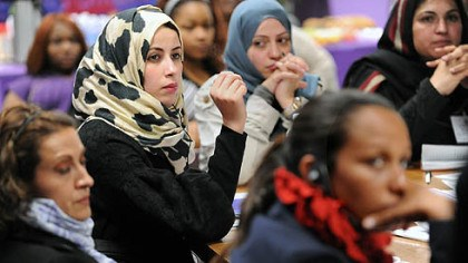 Hana Elhebshi Hana Elhebshi of Libya, center in the printed scarf, asks a question during a talk and reception for awardees at Gwen's Girls in Point Breeze.