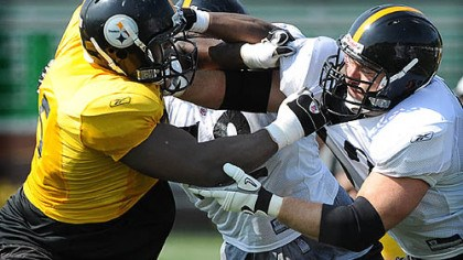 Hartwig Center Justin Hartwig blocks defensive end Ryan McBean during morning workouts yesterday.