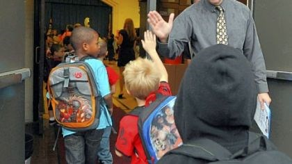 High-five arrival George Washington Elementary principal Paul Sweda gives high-fives to students Thursday as they arrive for the first day of school.