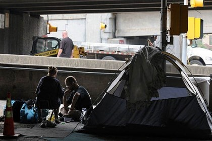 homeless camp Connie and Tony Ferguson sit at a tent under one of three overpasses over Anderson Street on the North Side, while a crew behind them begins moving the homeless encampment.