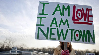 I am Newtown A Newtown, Conn., resident, who declined to give her name, sat at an intersection today holding a sign for passing motorists up the road from the Sandy Hook Elementary School, the scene of yesterday's massacre.