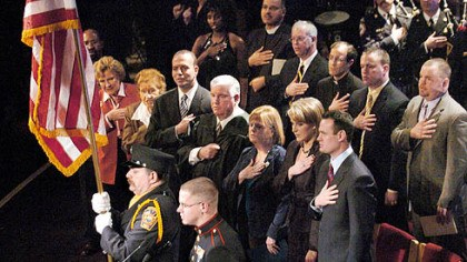 Inauguration of mayor Luke Ravenstahl, surrounded by family and friends and local and state politicians, pledges allegiance to the flag during his inauguration ceremony at Carnegie Museum Music Hall in Oakland. From left in the center row are Lt. Gov. Catherine Baker Knoll; former mayor Sophie Masloff; Allegheny County Chief Executive Dan Onorato; the mayor's father, Robert; mother, Cynthia; wife, Erin, and Mr. Ravenstahl.