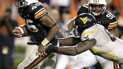 Interception Auburn linebacker Craig Stevens, left, intercepts a pass and returns it for a touchdown past West Virginia offensive line Selvish Capers, right, in last night's game.