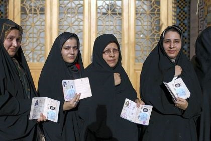 Iran Iranian women display their identification cards as they line up to vote in the presidential and municipal council elections Friday at an Iranian polling station in Qom, 78 miles south of the capital Tehran.