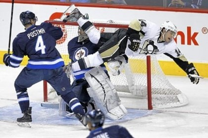 Jets Winnipeg Jets' Paul Postma sends Pittsburgh Penguins' Chris Kunitz flying in front of Jets goaltender Ondrej Pavelec during the first period.