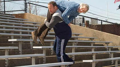 "Kevin James and Henry Wrinkler As Scott Voss, Kevin James carries Henry Winkler, who portrays a fellow teacher, over his shoulder as added weight while he works out for mixed martial arts fighting in ""Here Comes the Boom."""