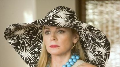 Kim Cattrall Samantha (Kim Cattrall) makes a statement with a big hat, belt and fancy cocktails.