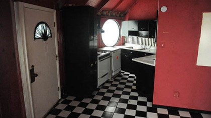 Kitchen The compact kitchen has bright-red walls, black wood cabinetry and a vintage black-and-white checkered linoleum floor.