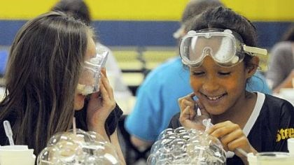 LabRatz science program Maranda Phillips, 10, and Maura Bryant, 9, fourth-graders at Cornell Elementary School in Coraopolis, take part in the LabRatz science program in which they were learning about the surface tension of water.