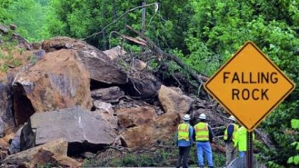 Landslide PennDOT officials are dwarfed by the boulders that landed on Route 88 in East Bethlehem, Washington County. PennDOT District 12 executive Joe Szczur said rock is still hanging about 80 feet above the road.