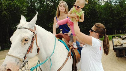 Littlest Palone Bethann Palone lifts the littlest Palone (for now), 2-year-old Alana into the saddle with Hannah.