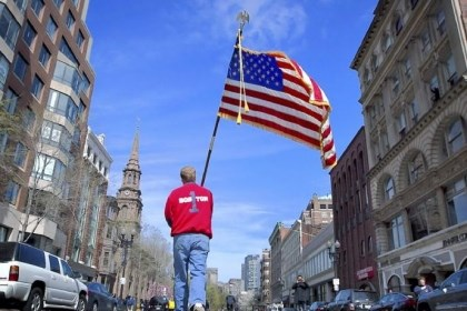 Lt. Mike Murphy Lt. Mike Murphy of the Newton, Mass., fire dept. carries an American flag down the middle of Boylston Street after observing a moment of silence at 2:50 p.m. Monday in honor of the victims of the bombing at the Boston Marathon.