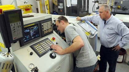 machine tool at APEX CNC Swiss Chuck Fluharty (right) watches Dallas Toth set up a machine tool at Fluharty's APEX CNC Swiss company.
